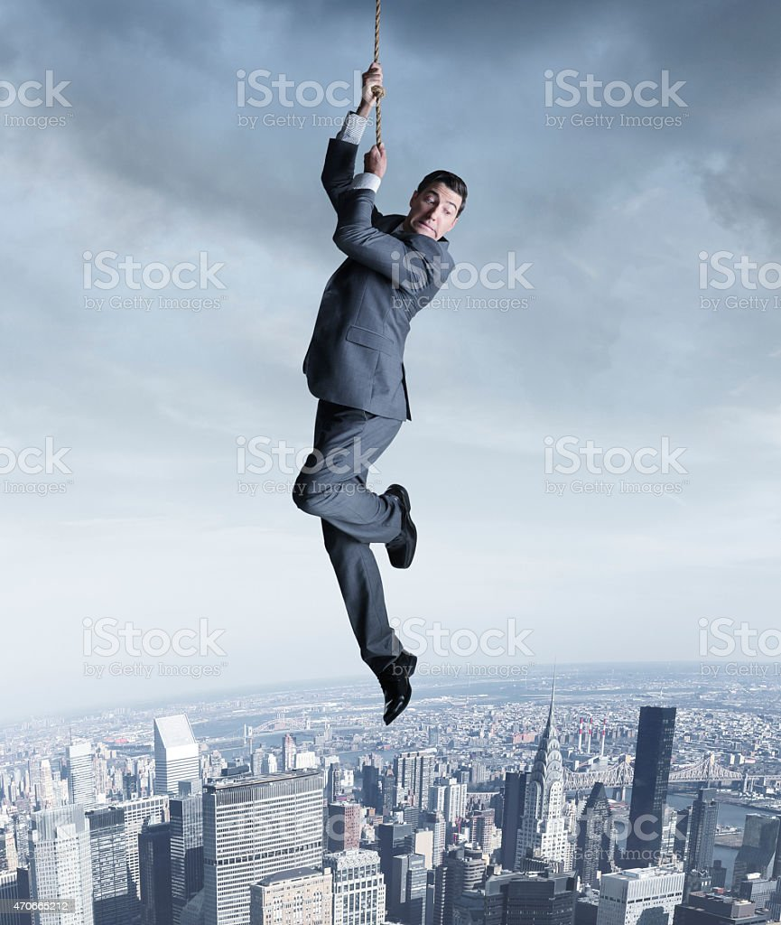 Businessman hanging on to a rope above city stock photo