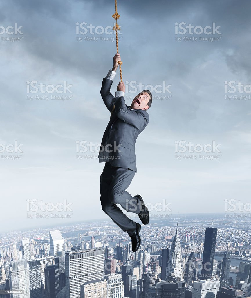 Businessman hanging on to fraying rope above city stock photo
