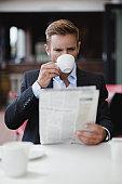 Businessman having coffee with newspaper