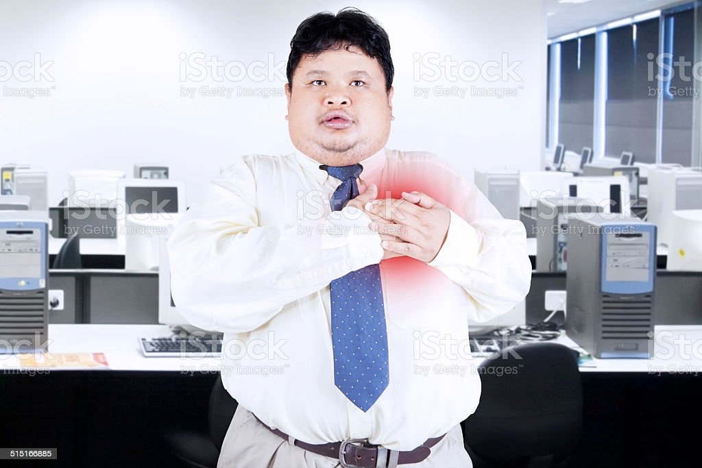 Businessman having heart attact in office stock photo