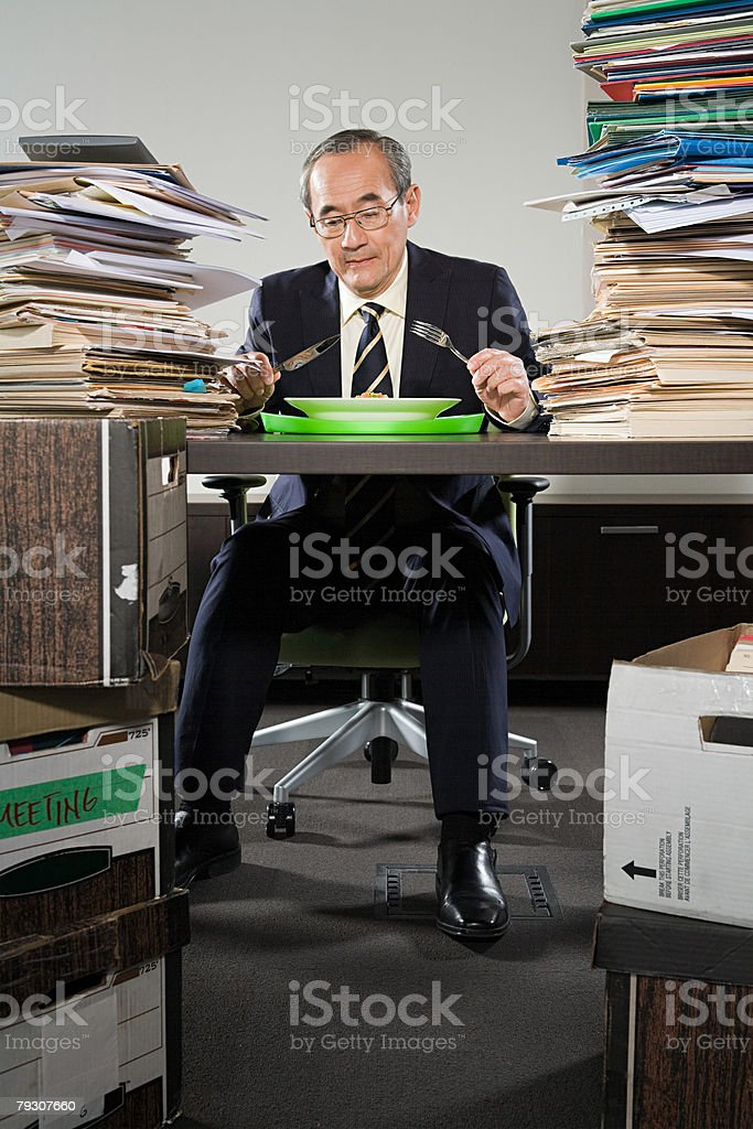 A businessman having his dinner at his desk stock photo