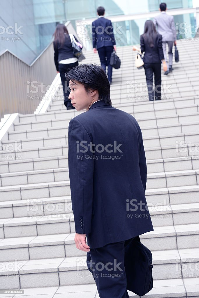 Businessman hesitating, collegues moving forward stock photo