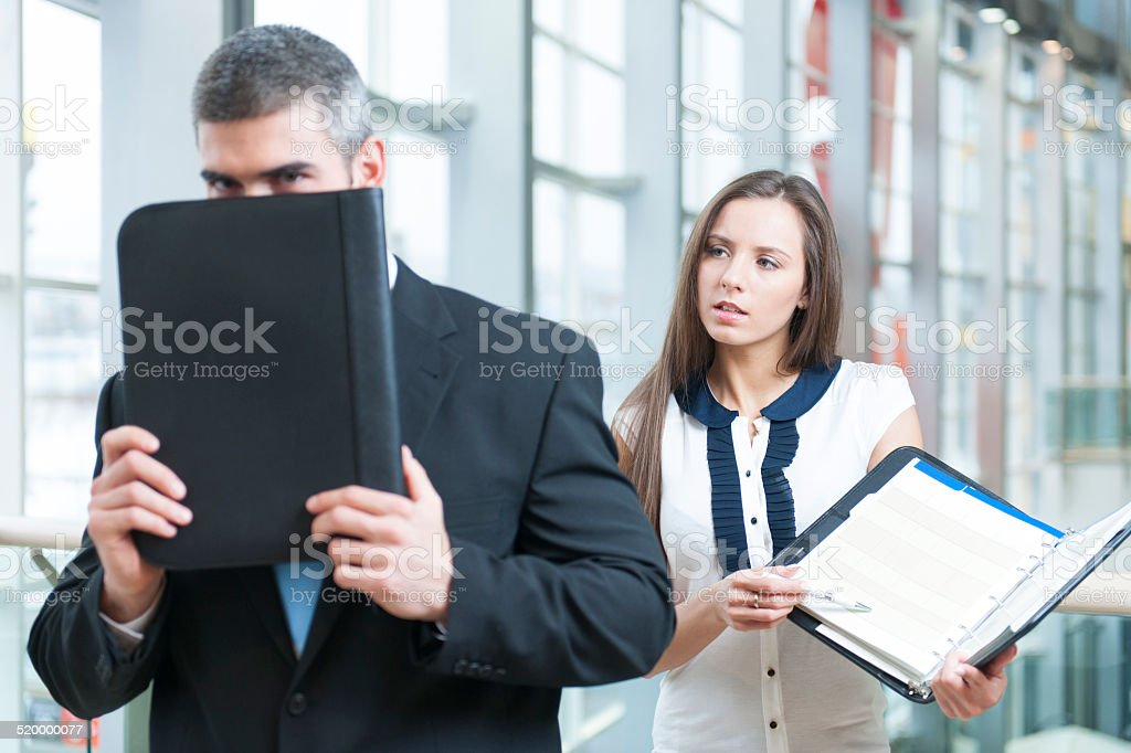 Businessman hides from coworker behind folder stock photo