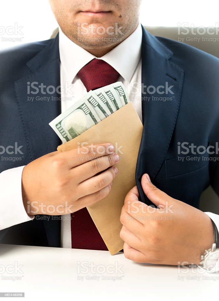 businessman hiding envelope with money in pocket at jacket stock photo