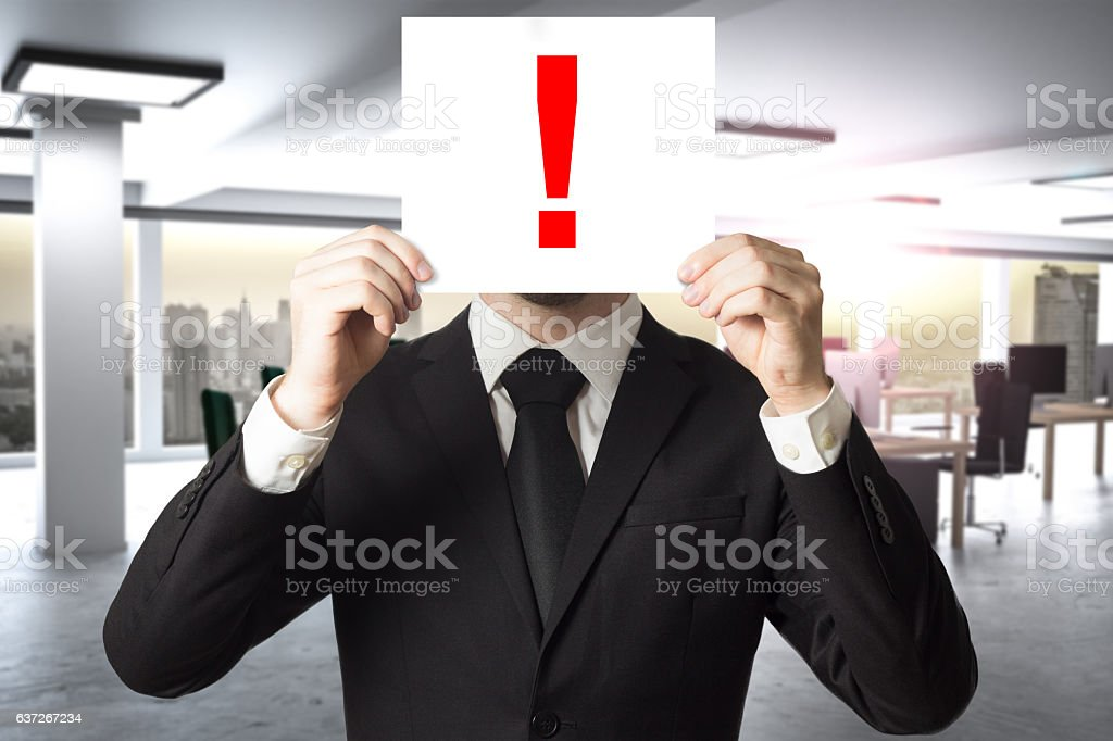 businessman hiding face behind exclamation mark red stock photo