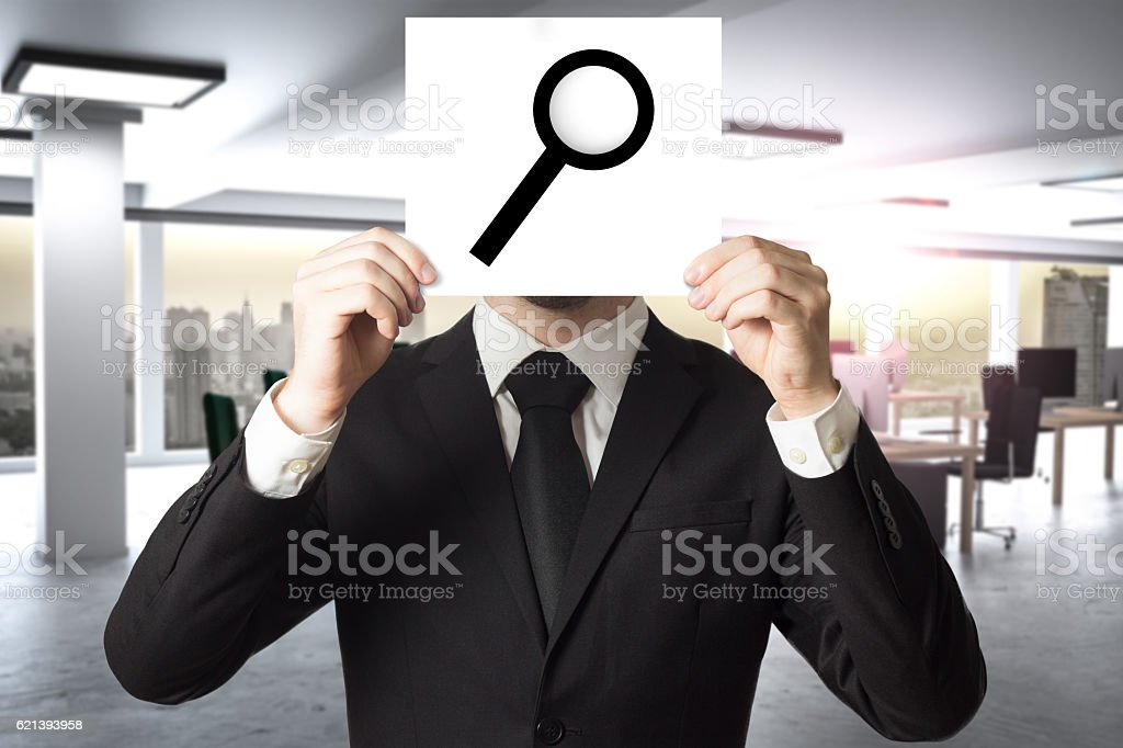 businessman hiding face behind sign loup magnifier stock photo