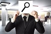 businessman hiding face behind sign loup magnifier