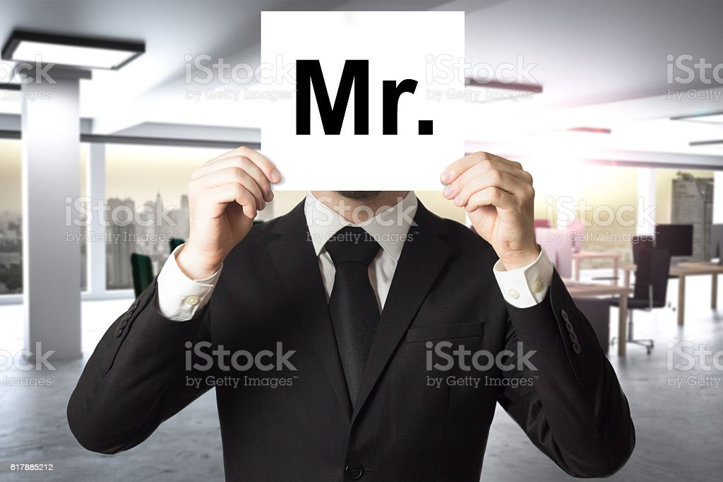 businessman hiding face behind sign mister stock photo