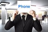 businessman hiding face behind sign phone