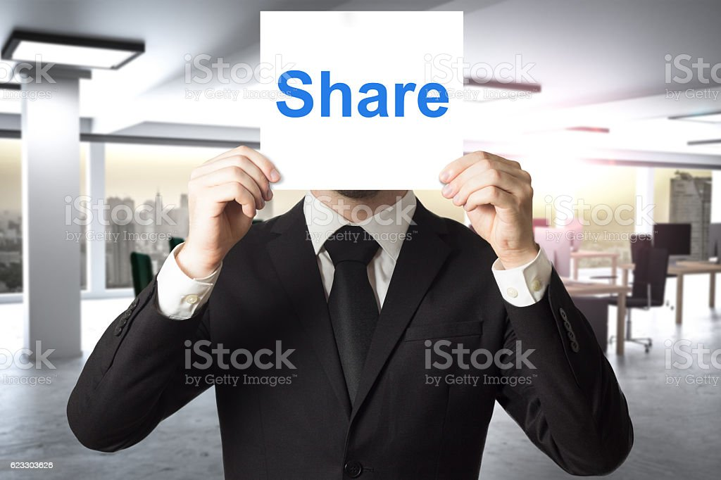 businessman hiding face behind sign share stock photo