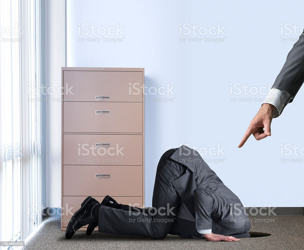 Businessman Hiding Head In Hole As Boss Points At Him stock photo