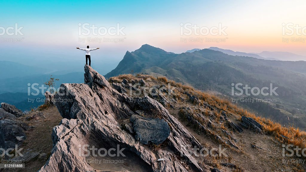 businessman hike on the peak of rocks mountain at sunset stock photo