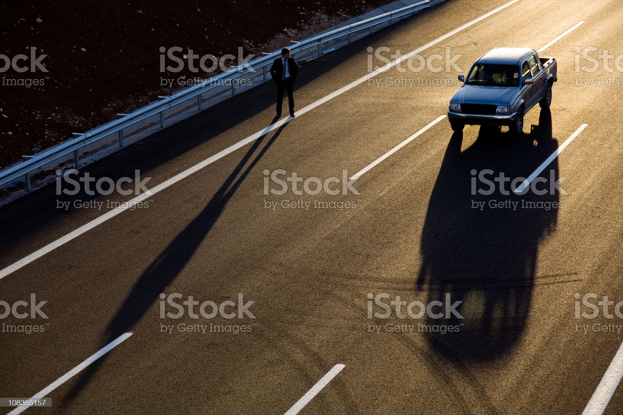 Businessman hitchhiking on the road side royalty-free stock photo