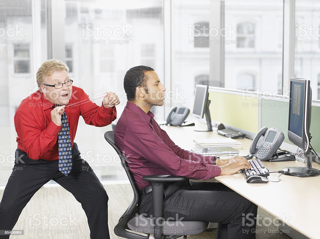 Businessman hitting co-worker with rubber band stock photo