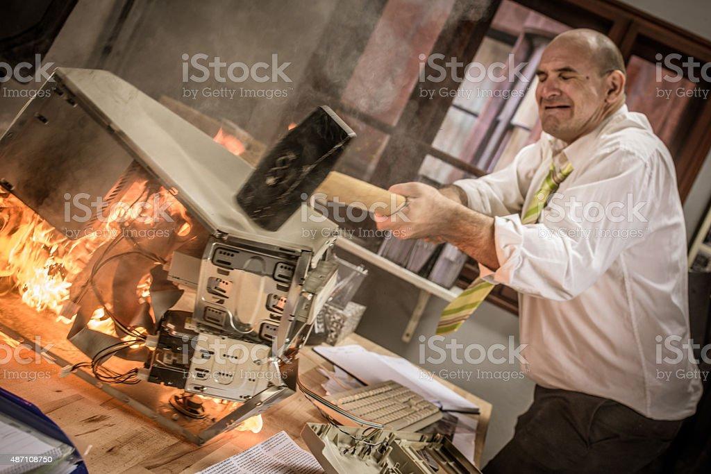 Businessman hitting hammer on burning CPU stock photo