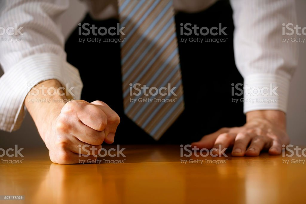 Businessman hitting table with clenched fist. stock photo