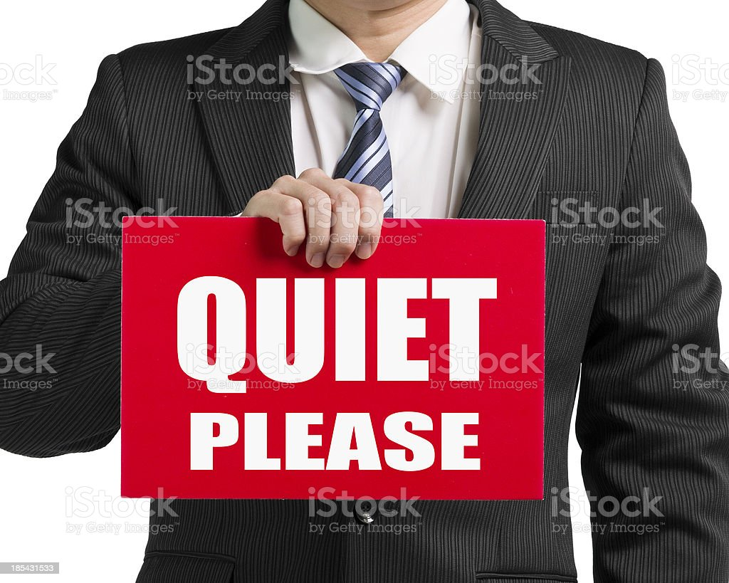 Businessman hold a red board with words 'QUIET PLEASE' stock photo