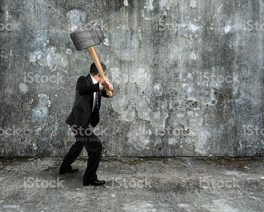 Businessman hold sledgehammer to crack old mottled concrete wall stock photo
