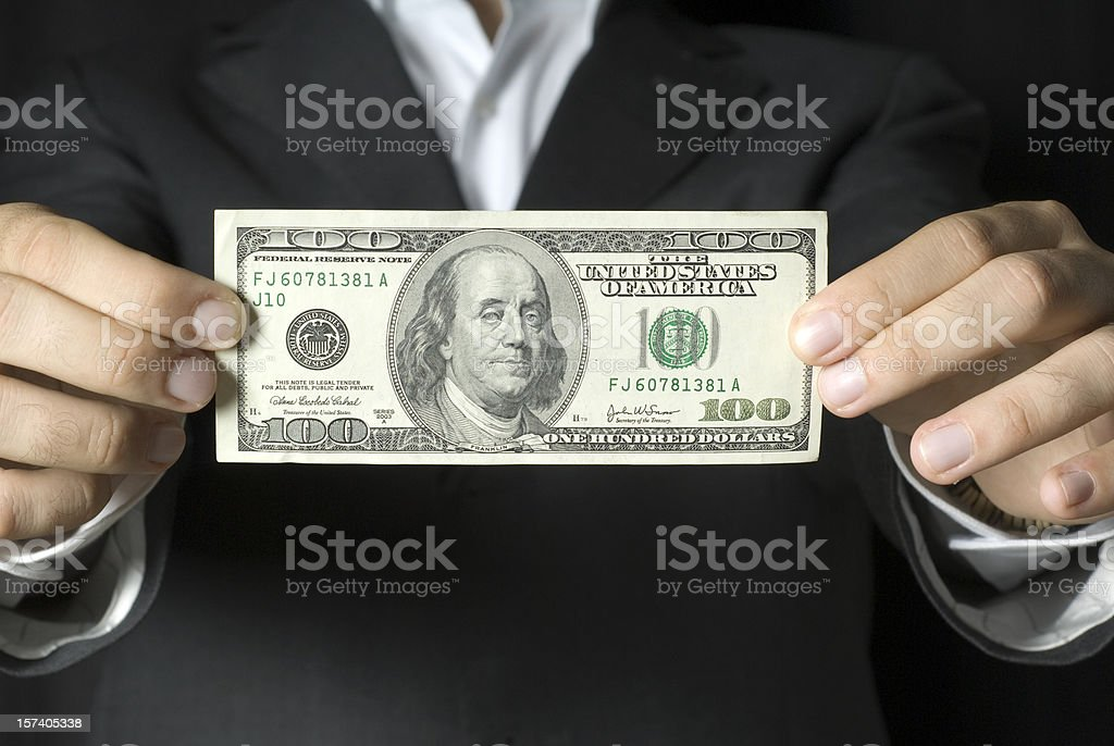 Businessman holding $100 US note royalty-free stock photo