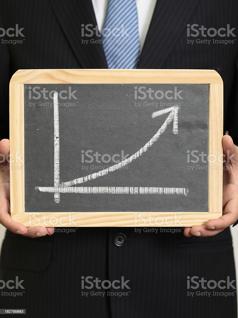 Businessman holding a blackboard with an increasing graph royalty-free stock photo