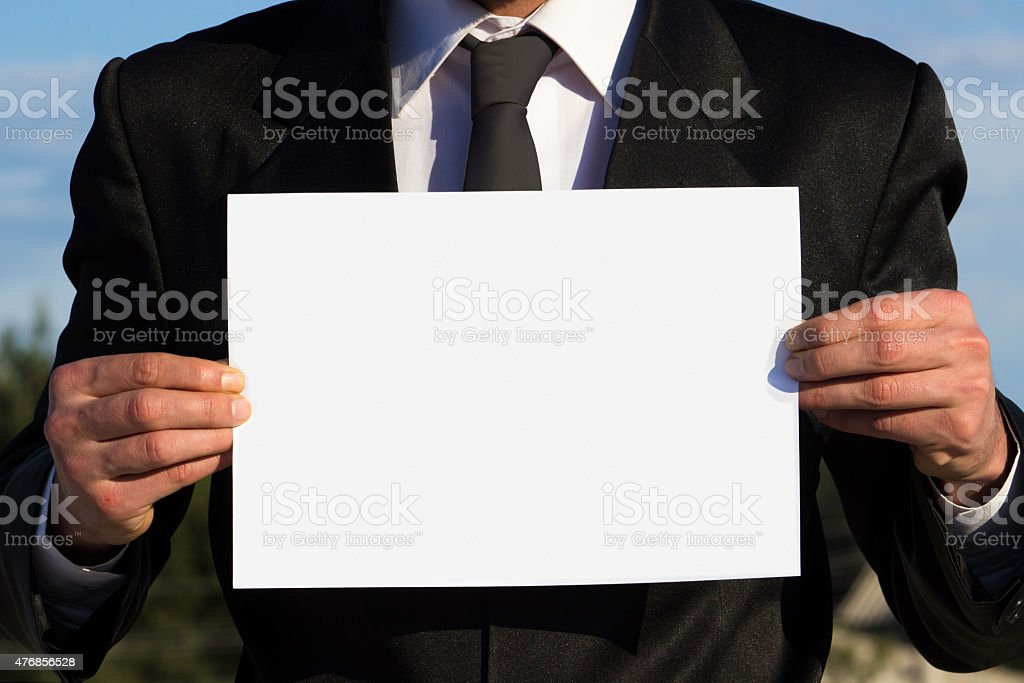 Businessman holding a blank sign for your text stock photo