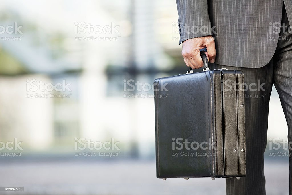 Businessman Holding a Briefcase Outdoors stock photo