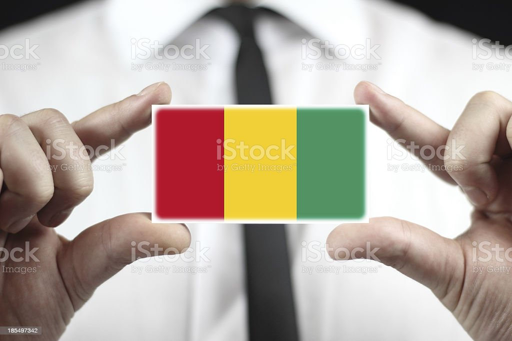 Businessman holding a business card with Guinea Flag royalty-free stock photo