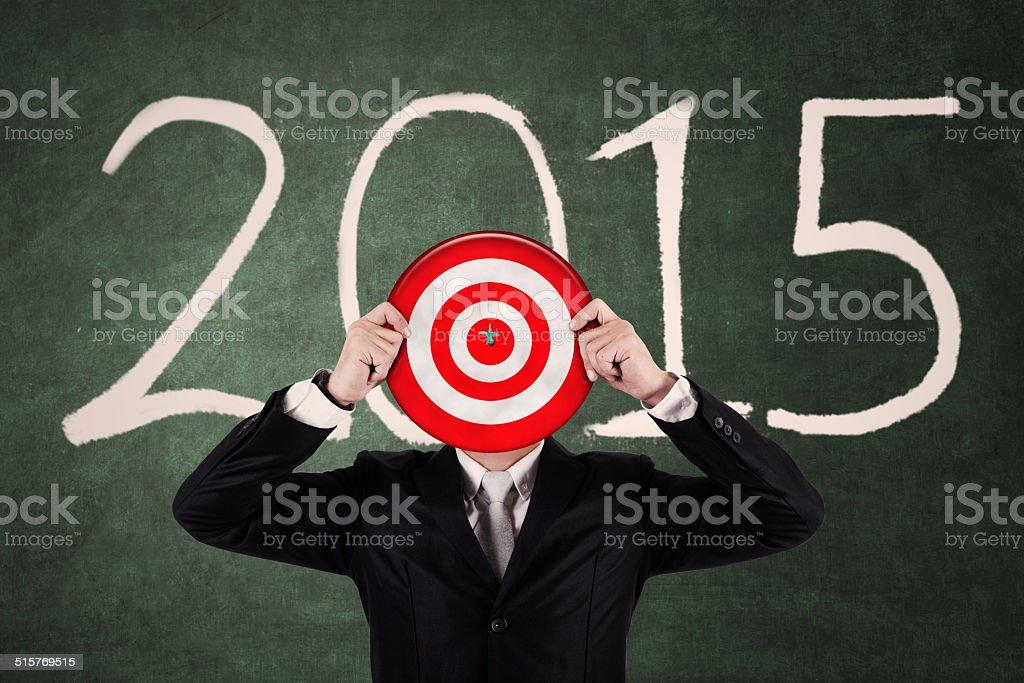 Businessman holding a dartboard stock photo