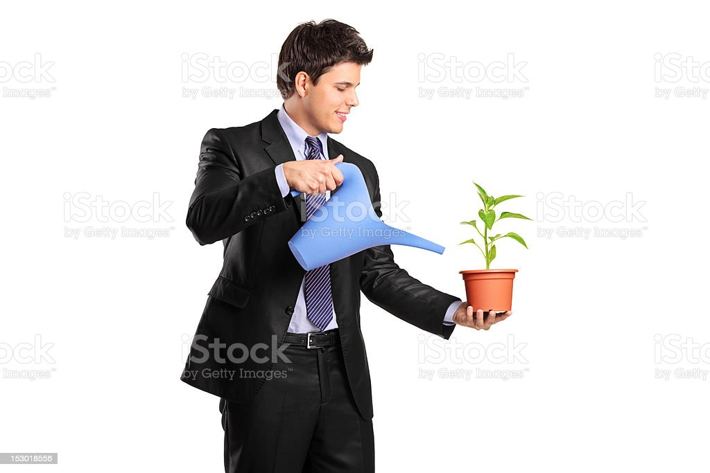 Businessman holding a flower and watering can royalty-free stock photo