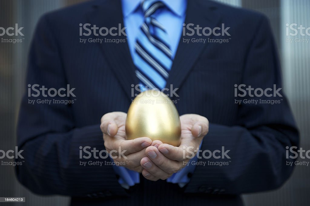 Businessman Holding a Golden Nest Egg Investment royalty-free stock photo