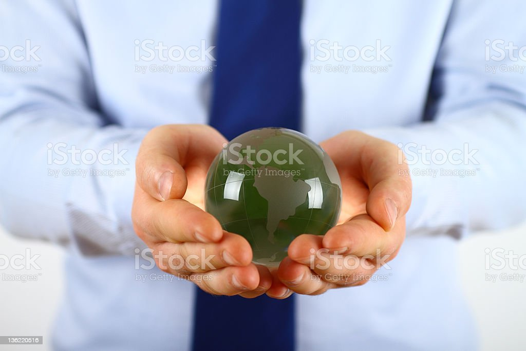A businessman holding a green globe royalty-free stock photo