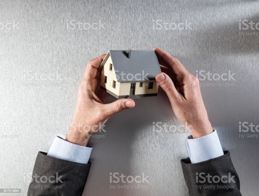 businessman holding a house for home valuation or property sale stock photo