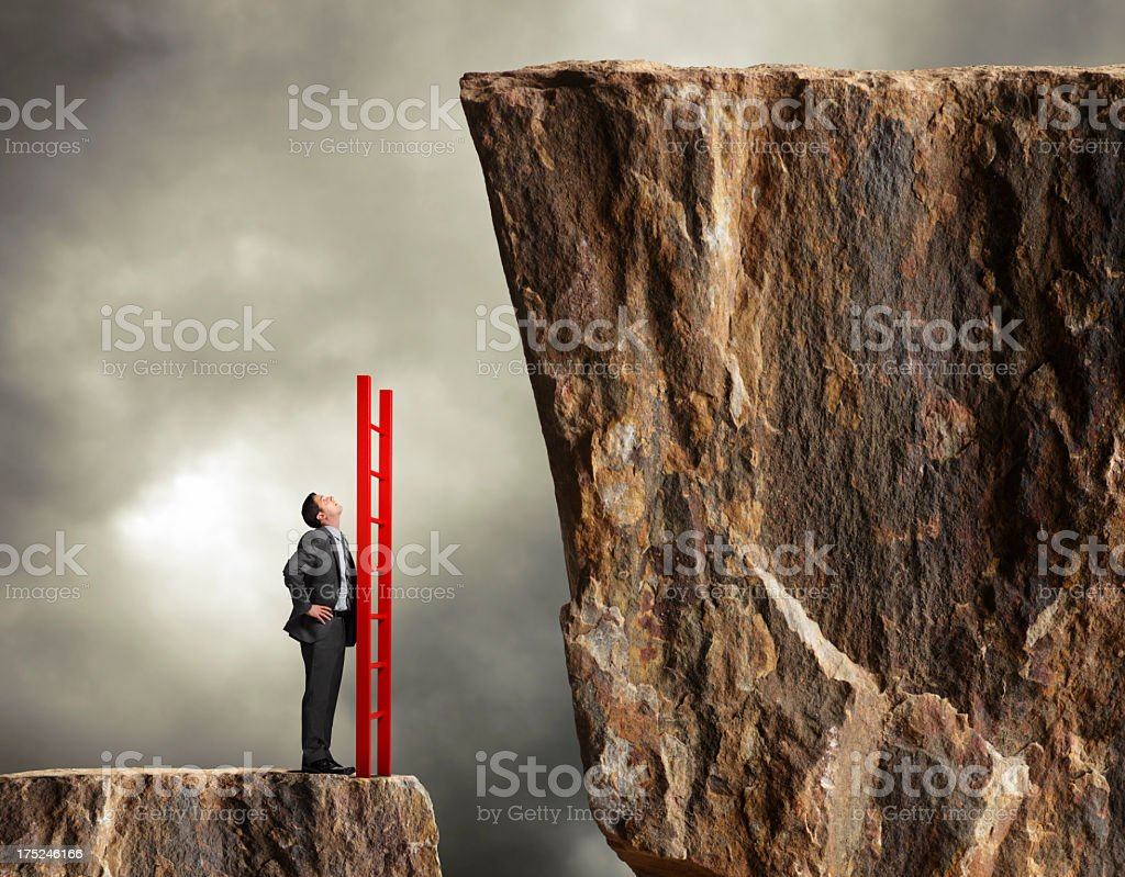 Businessman holding a ladder looks up towards higher level stock photo