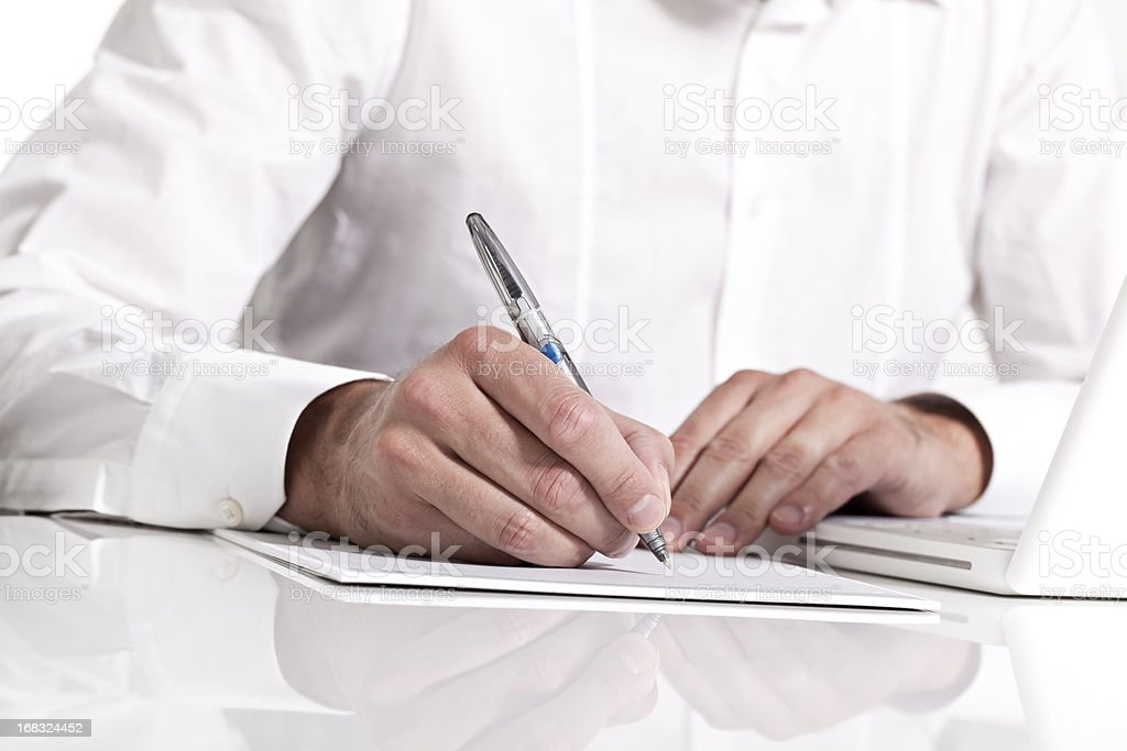 Businessman holding a pen & taking notes on paper stock photo