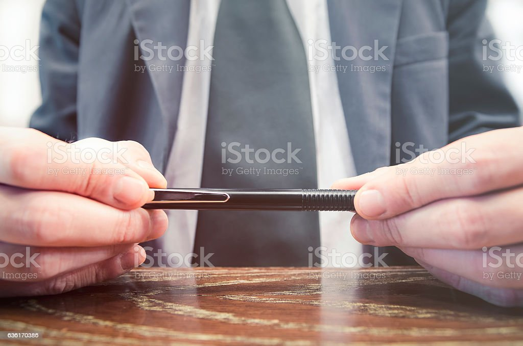Businessman holding a pencil while thinking. stock photo