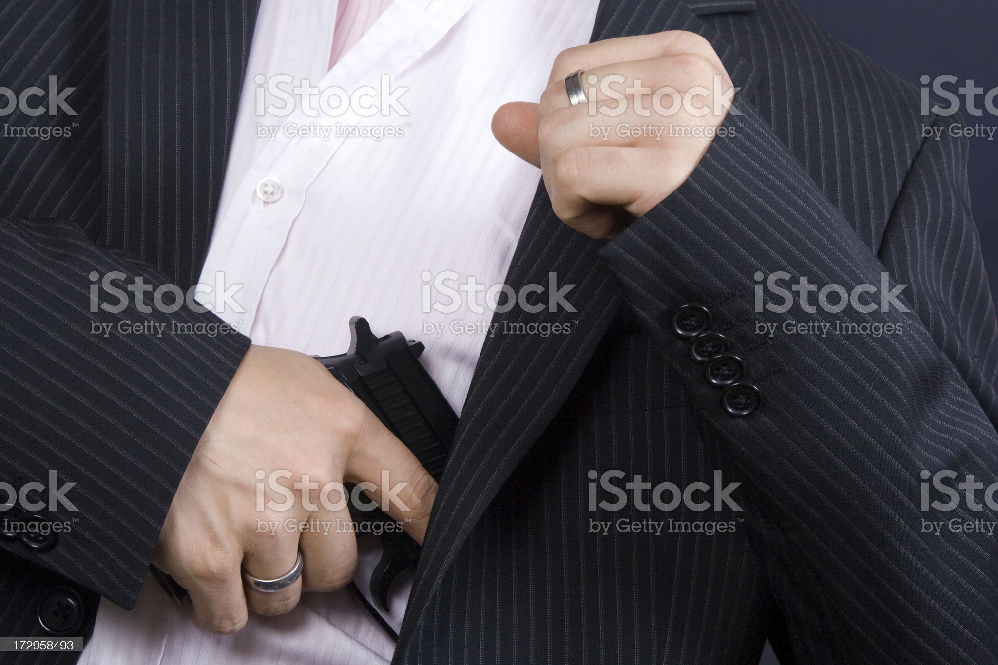 Businessman holding a pistol behind suit royalty-free stock photo