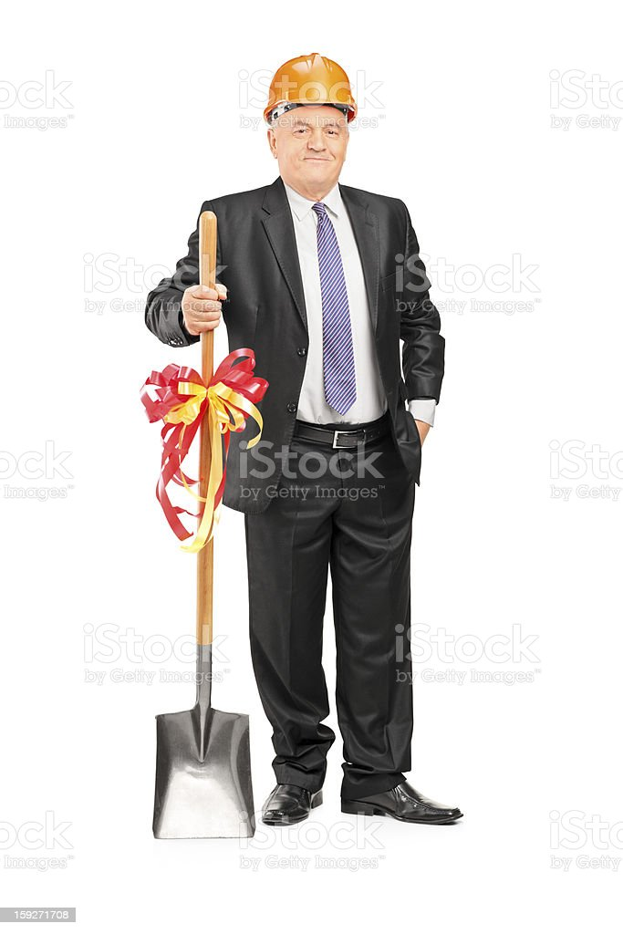 Businessman holding a shovel with ribbon on it stock photo