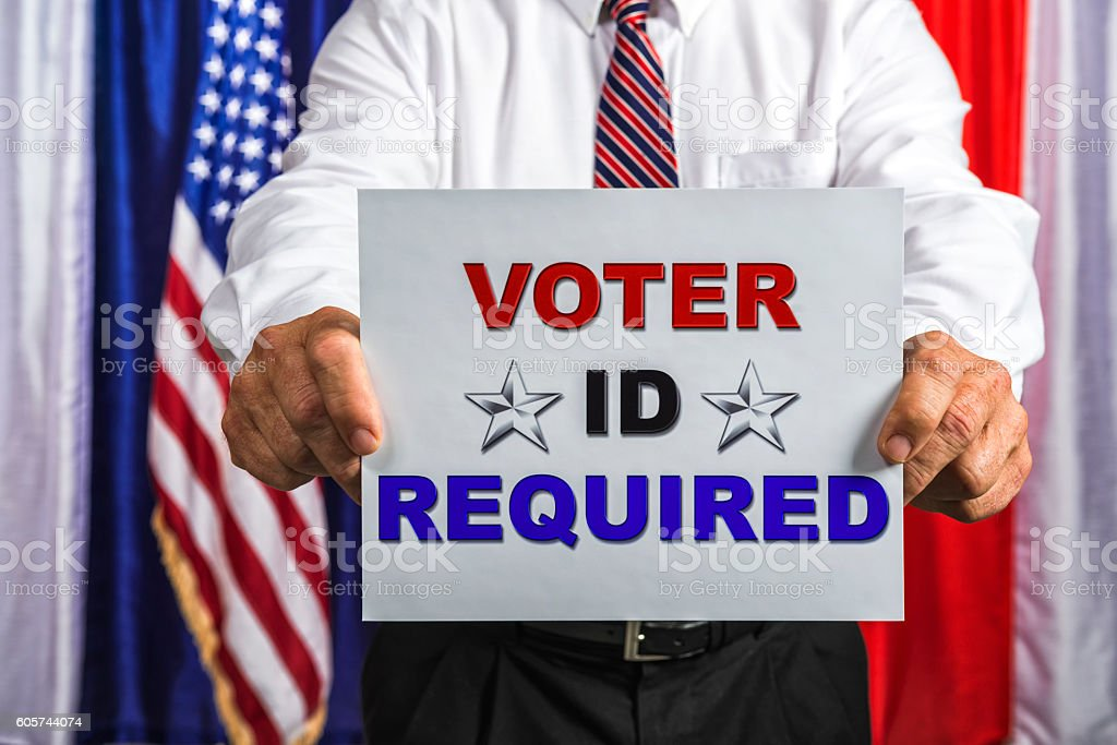 Businessman holding a sign that reads Voter ID Required stock photo