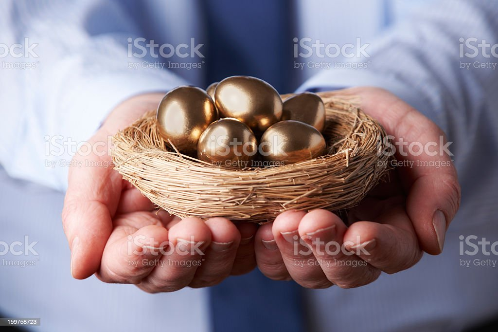 Businessman holding a small nest full of golden eggs stock photo