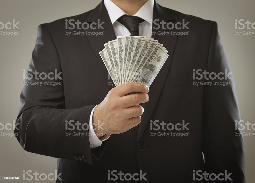 Businessman holding a stuck of money royalty-free stock photo