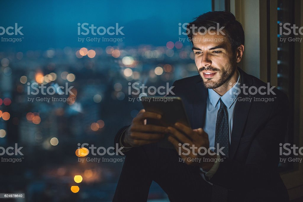 Businessman holding a tablet at night stock photo