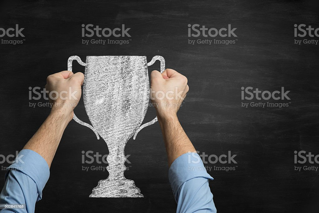 Businessman holding a trophy  drawn on blackboard stock photo