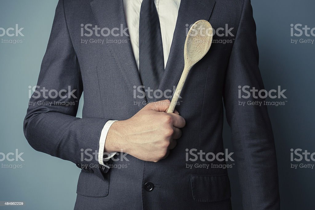 Businessman holding a wooden spoon royalty-free stock photo