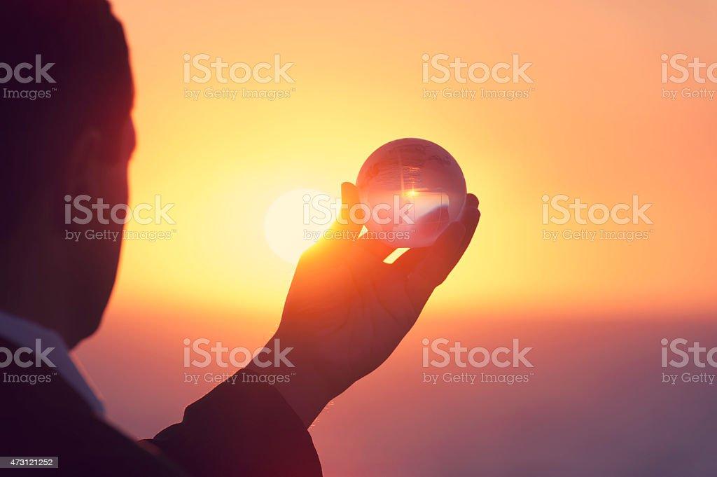 Businessman holding a world globe at dawn stock photo