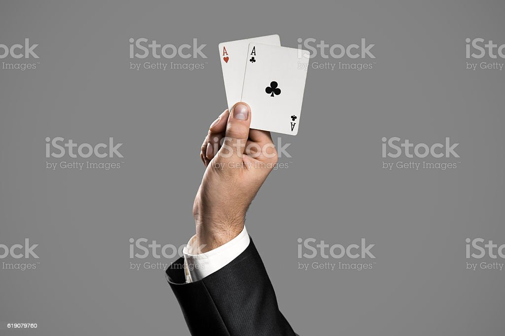 Businessman Holding Aces On Gray Background. Ace In The Hole stock photo