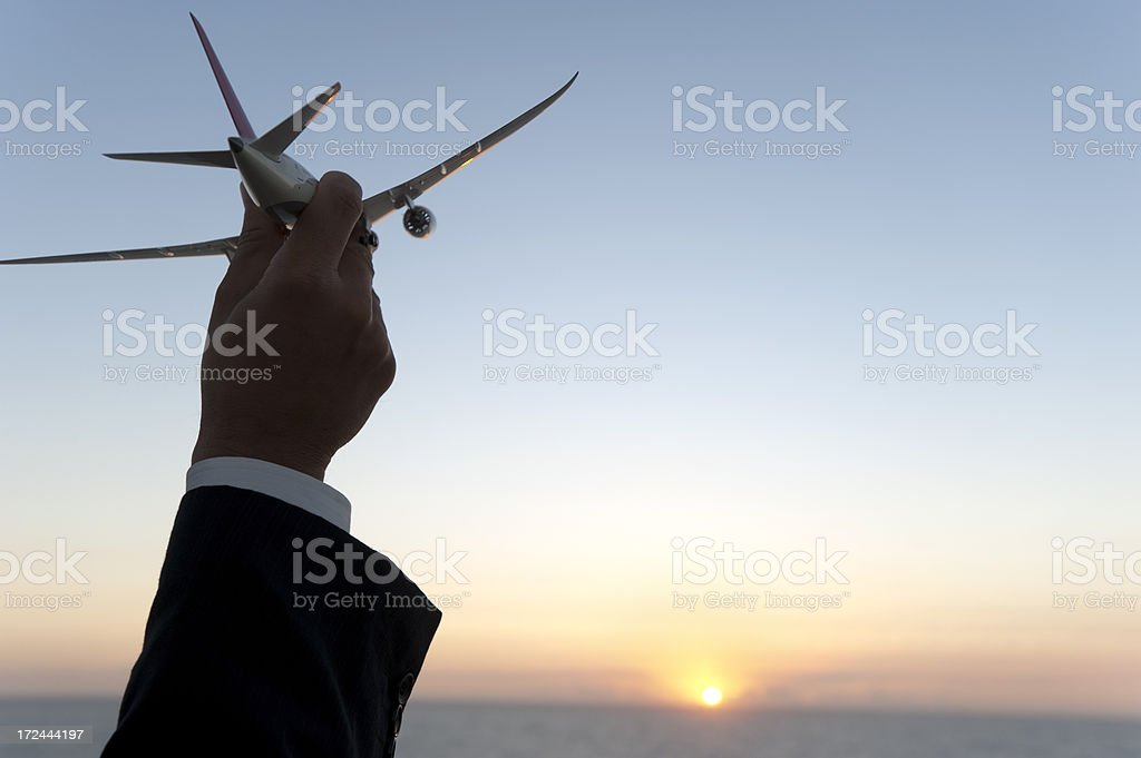Businessman holding airplane at sunrise royalty-free stock photo