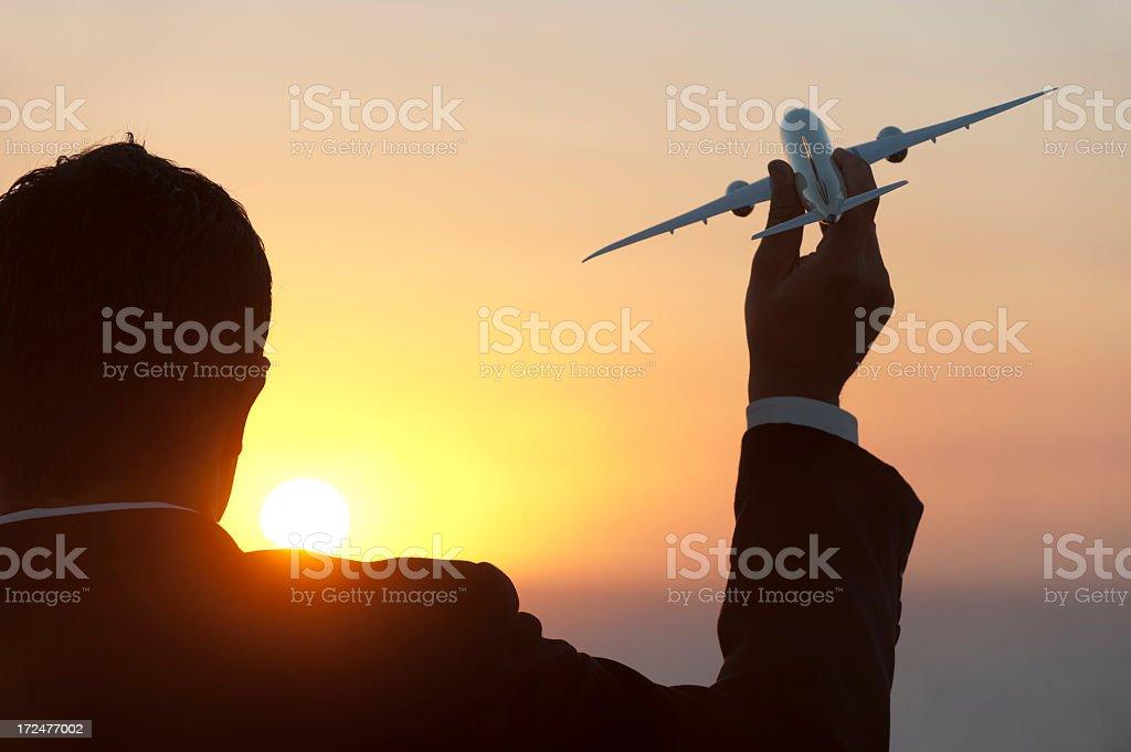 Businessman holding airplane at sunrise royalty-free stock photo