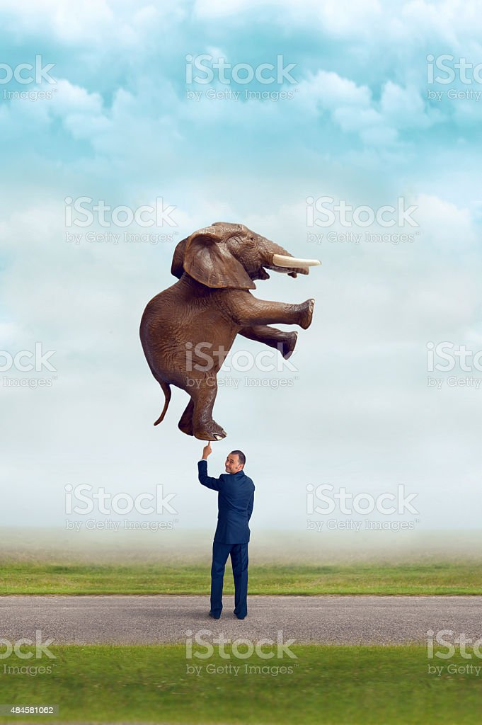 businessman holding an elephant with one finger stock photo