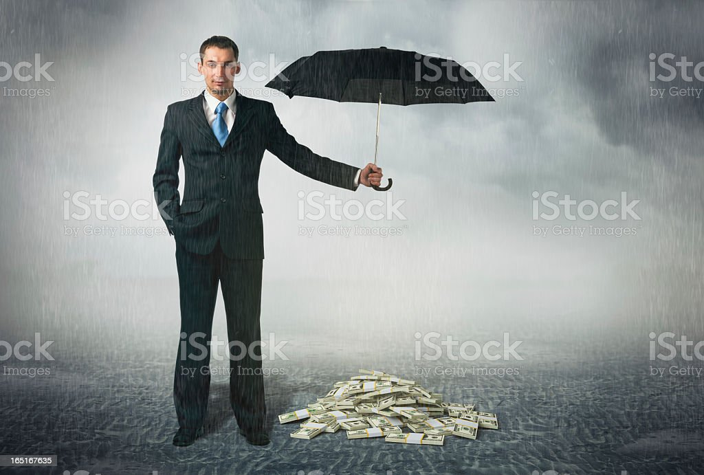 Businessman holding an umbrella over a pile of money stock photo