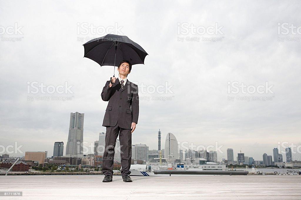 A businessman holding an umbrella royalty-free stock photo
